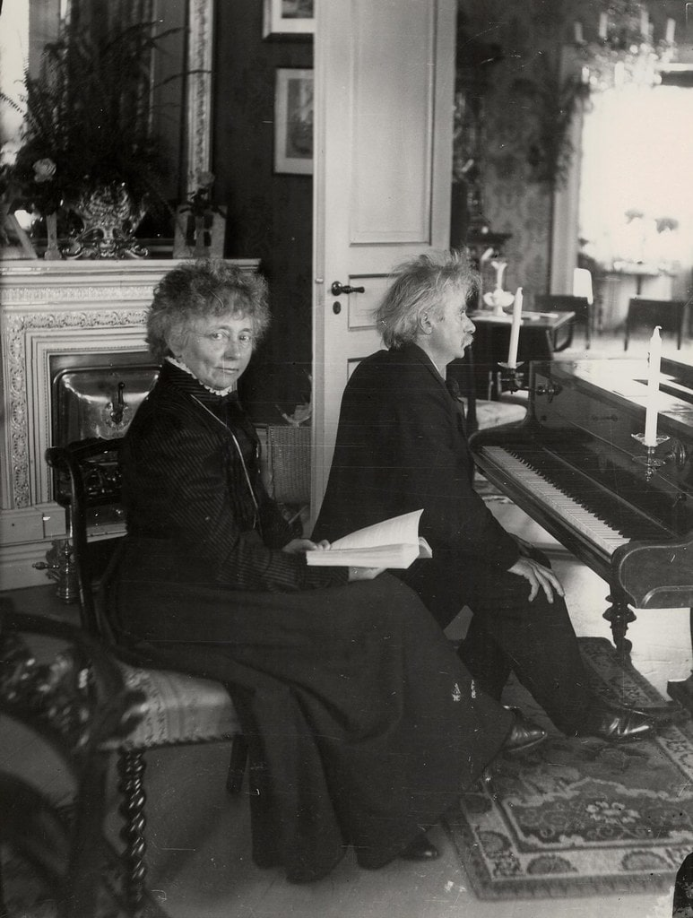 Photograph of Edvard Grieg and his wife with Grieg playing piano and his wife sitting next to him